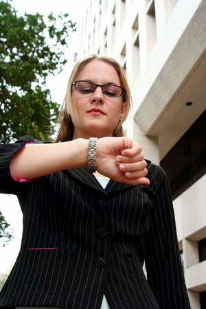 Businesswoman looking at watch in front of office building Stock Photo - 773065