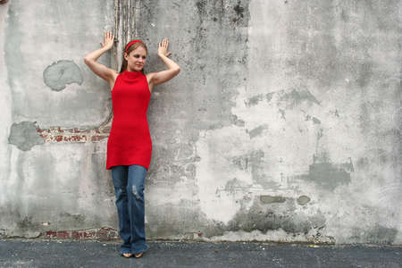 Young woman standing against grey wall Stock Photo