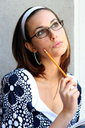 Head shot of female student in glasses holding pencil to her face