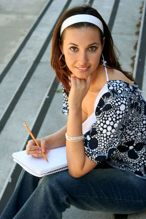 Female student sitting on stairs with a notebook and pencil Banco de Imagens