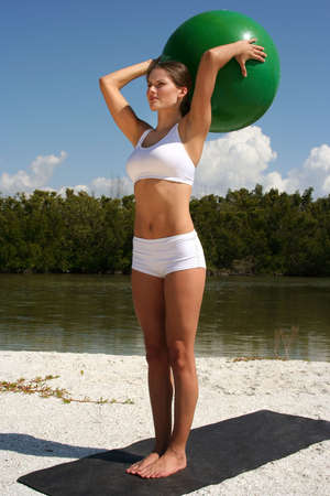 Attractive woman on beach doing yoga poses with ball