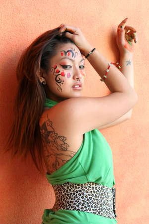 Head shot of young asian woman with piercing in nose and lip putting paint on her face photo