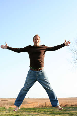 Young man jumping against a blue sky Stock Photo