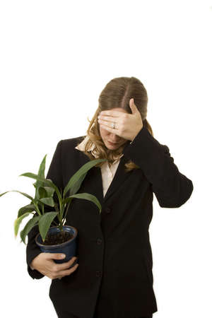 Businesswoman isolated on white holding plant looking as if she has just been fired photo
