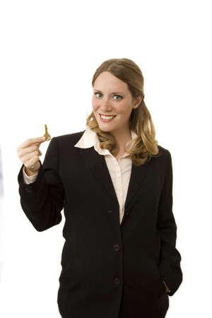 Female realtor on white background holding a key Stock Photo