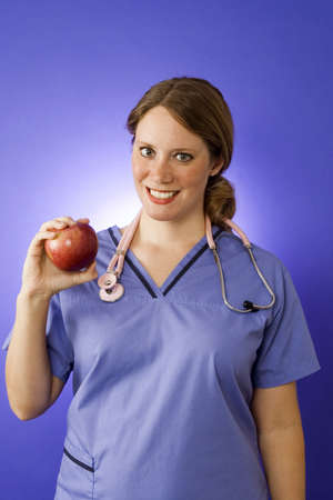 Female doctor in blue scrubs holding an apple