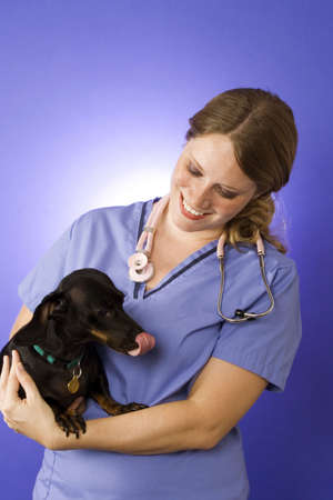 Female vet in blue scrubs with a black dog Banco de Imagens - 1064788