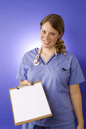 Female doctor in blue scrubs with a blank clipboard