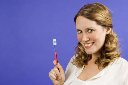Young woman on blue holding a toothbrush photo