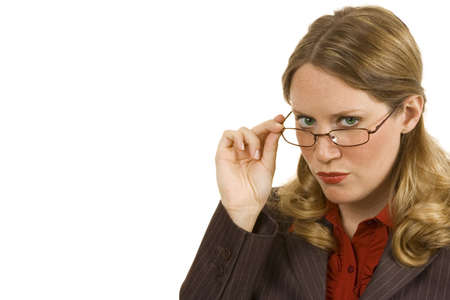 sternly: Businesswoman on white looking sternly over her glasses