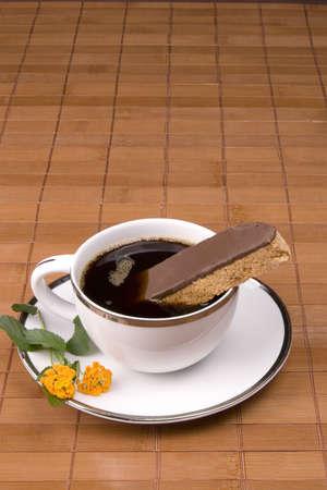 Witte thee kop op bruine achtergrond met bloemen en biscotti cookie. Stockfoto