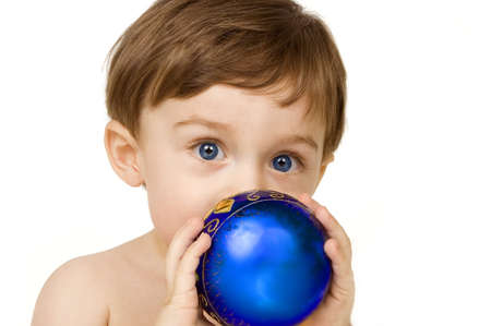 Baby on white playing with a Christmas ornament. photo