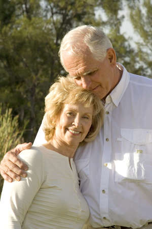 Happy senior couple sitting in a park. photo