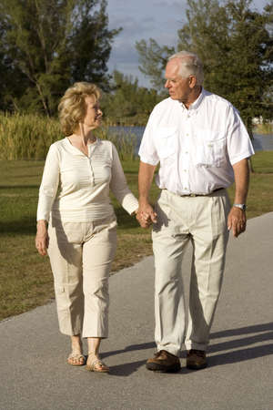 Happy senior couple walking in a park photo