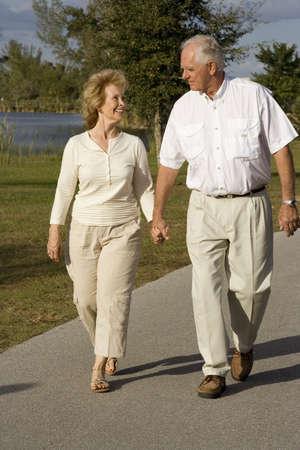parejas caminando: Feliz altos joven caminando en un parque