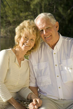 Happy senior couple sitting in a park.