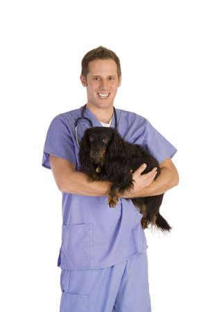 Veterinarian on white holding a black dog.