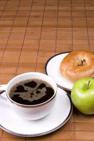 Coffee bagel and apple on a brown background. photo