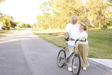 Attractive and fit seniors on bikes outdoors. photo
