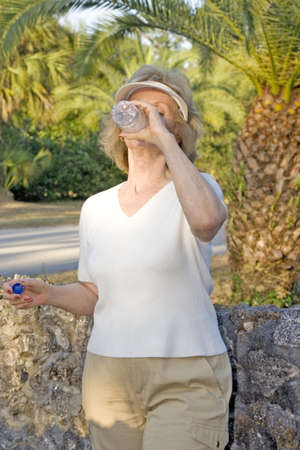 man drinking water: Happy senior woman drinking water after a walk