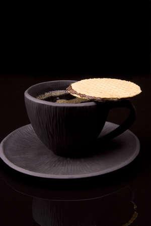 Zwarte thee beker op zwarte achtergrond met cookie