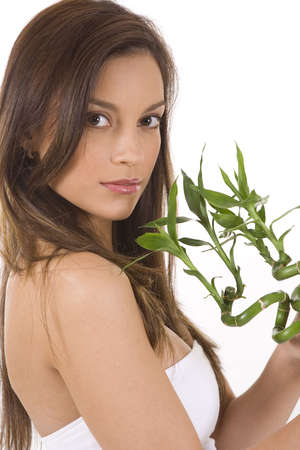 Young woman on white holding green bamboo. Stock Photo - 5088589