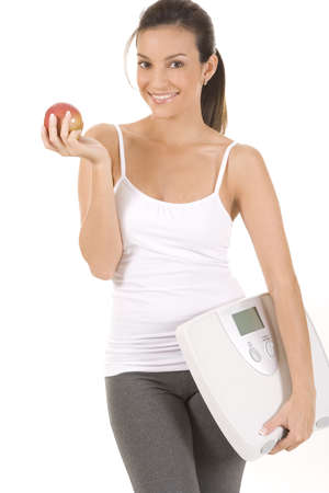Woman on white holding an apple and scale Stock Photo - 5088584