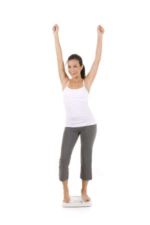 weight gain: Woman on white standing on scale looking happy. Stock Photo