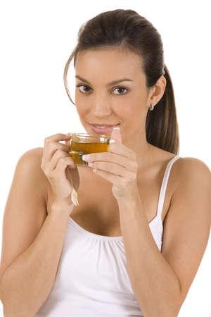 お茶を一杯と白い背景の上の若い女性 写真素材