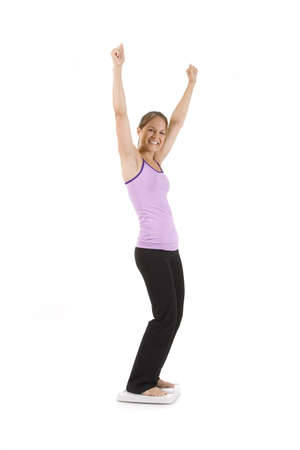 gain: Woman on white standing on scale looking happy.  Stock Photo