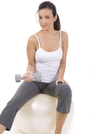 Woman on white holding silver dumbbells on a ball photo