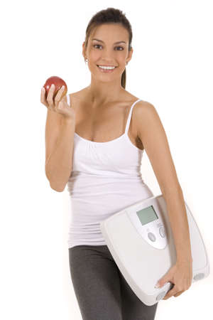 Woman on white holding an apple and scale
