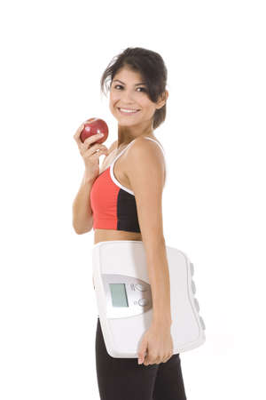Woman on white holding an apple and scale Stock Photo - 5215059