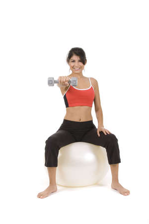 curls: Woman on white holding silver dumbbells on a ball Stock Photo