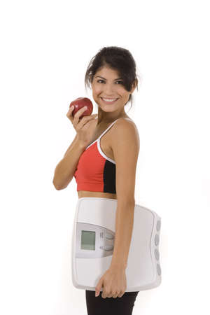 Woman on white holding an apple and scale Stock Photo - 5226317