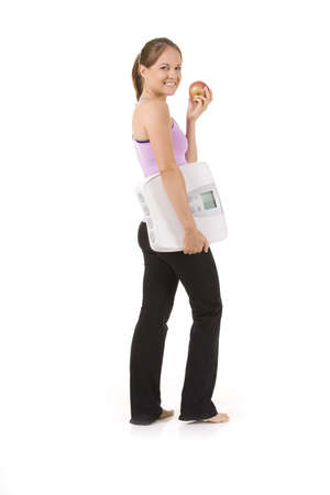 Woman on white holding an apple and scale Stock Photo - 5239600