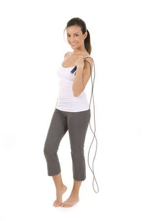 Woman on white holding a jump rope.  Imagens