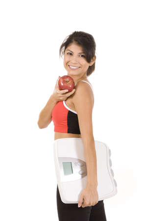 Woman on white holding an apple and scale  Stock Photo - 5262999