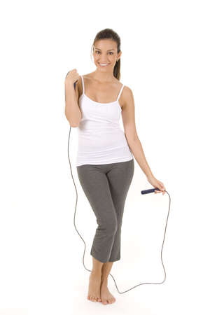 Woman on white holding a jump rope.  photo