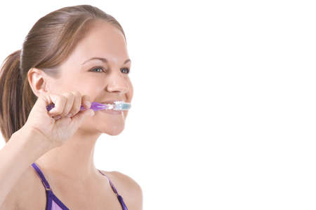 Beautiful woman on white brushing her teeth. photo