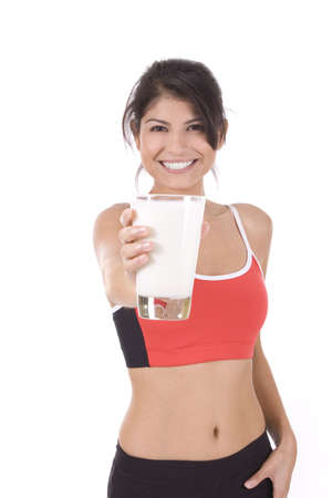 Beautiful woman holding a glass of milk on white. Imagens