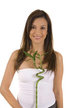 Young woman on white holding green bamboo. photo