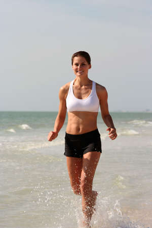running water: Attractive woman working out on the beach