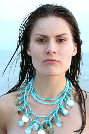 Close up of woman on beach with sand on her face. photo