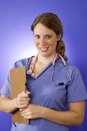 Young nurse in blue scrubs writing on a clipboard. Stock Photo - 5898897