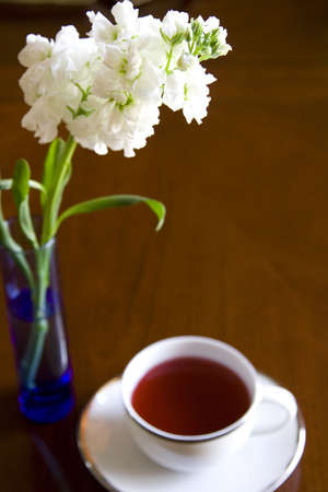 daises: White tea cup with with flowers in vase Stock Photo