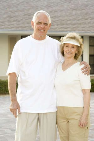 Happy senior couple standing in front of their home. photo