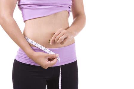 cintura: Mujer sobre fondo blanco, medir la cintura con cinta m�trica. Foto de archivo