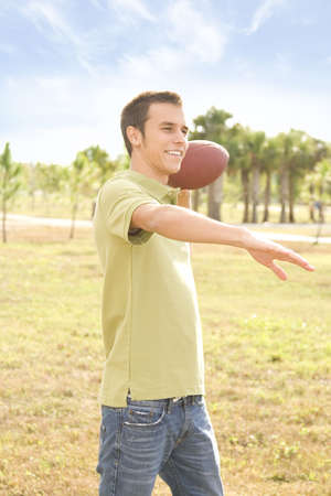 Attractive young man outside holding an american football photo
