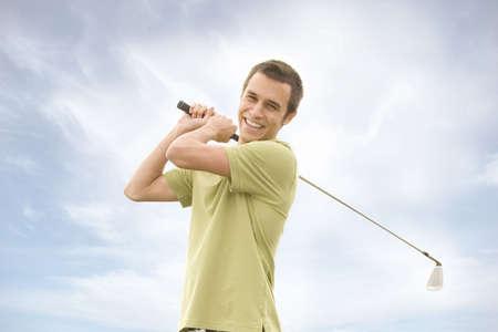 golfing: Mensen tegen blauwe hemel met golfclubs